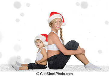 woman with child sitting on snow in Santa hats - woman with...