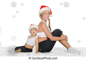 family sits in snow in Santa hats and clothing for fitness