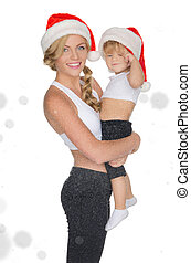 woman holding child in Santa hats and clothing for fitness...