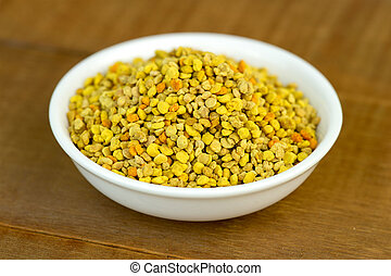 Bee pollen closeup in white bowl on wooden table