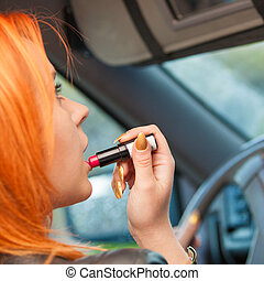 girl painting her lips doing make up while driving the car....