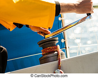 Winch capstan with rope on sailing boat. - Male hand on...