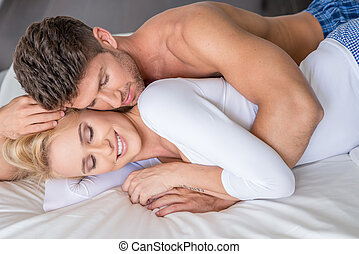Romantic Couple Lying on White Bed - Close up Romantic Young...