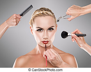 Picture shows studio makeup process of a young pretty girl