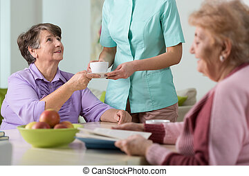 Serving the tea - Young nurse serving the tea to two older...
