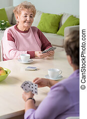 Playing cards - Two senior women playing cards in lounge