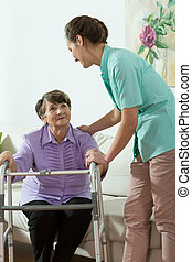 Nurse helping older lady - Young pretty nurse helping older...