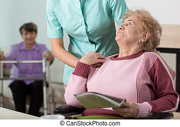 Therapist in nursing home - Young caring therpist and senior...