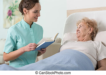 Reading to older woman - Young beautiful nurse reading to...