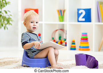 toddler sitting on chamber pot playing tablet pc with toilet...