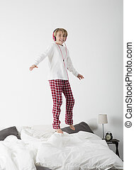 Little girl with Headphones jumping in bed
