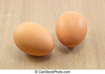 Two raw eggs on wood board