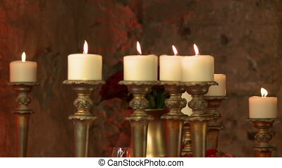 Candles in golden candlesticks as element of decor