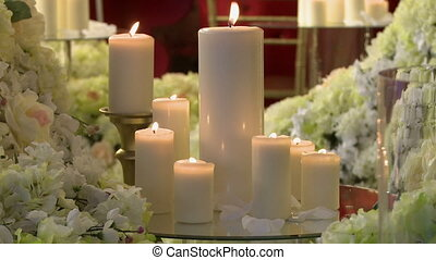 Lighted candles of different heights and flowers - Lighted...