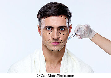 Handsome man at plastic surgery with syringe in his face