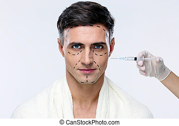 Man at plastic surgery with syringe in his face