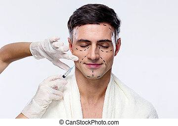 Man with closed eyes at plastic surgery with syringe in his...