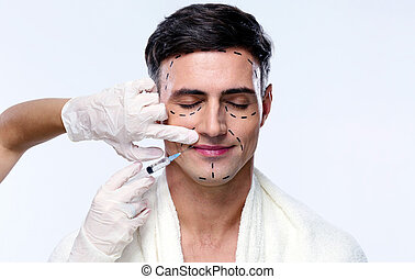 Handsome man with closed at plastic surgery with syringe in...