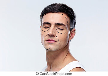 Man with closed eyes and marked with lines for plastic...