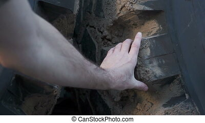 Mechanic Reaches Inspecting Tire - Point of view shot of a...
