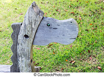 Wooden horse in the playground of small park.