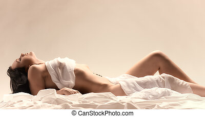 Woman and white sheets - Attractive seminude woman wearing...