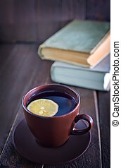 tea with lemon in cup and old books