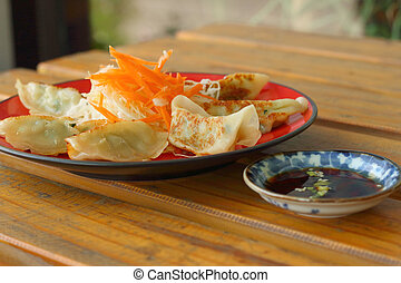 Gyoza in a red plate on a table