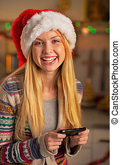 Happy teenager girl in santa hat writing sms