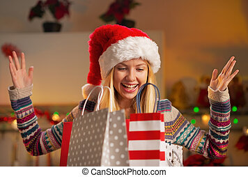 Portrait of happy teenager girl in santa hat with shopping...