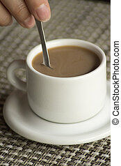 Hand stirring spoon in cup of coffee expresso - Hand of...