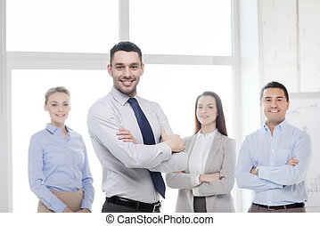 smiling businessman in office with team on back - business...