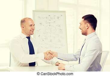 two smiling businessmen shaking hands in office - business...
