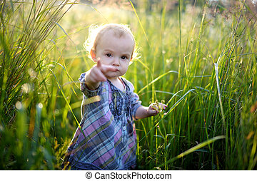 Little baby in an overgrown grass pointing at you - Little...