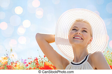 smiling young woman in straw hat on poppy field