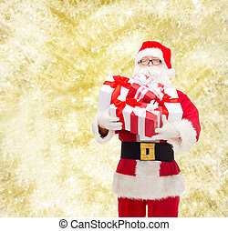 man in costume of santa claus with gift boxes - christmas,...