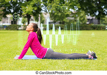 smiling woman stretching back on mat outdoors - fitness,...