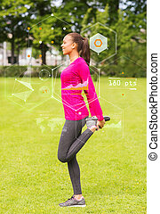 smiling woman stretching leg outdoors - fitness, sport,...