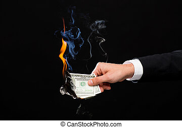 close up of male hand holding burning dollar money -...