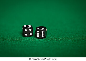 close up of black dice on green casino table - gambling,...