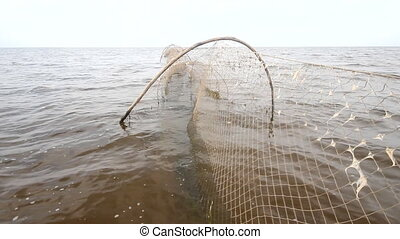 fishing net a fish-trap on lake - industrial net trap on...