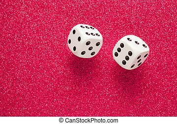 White dice - Rolling white dice over red glittering surface
