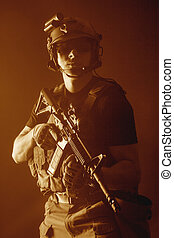 Private military contractor PMC with assault rifle on dark...