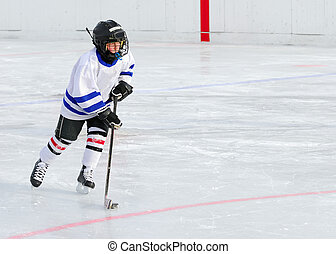 Hockey Player on Ice - A young hockey player races with the...