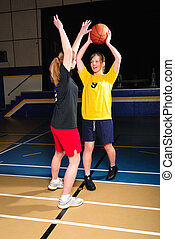 Basketball Players - Two women playing basketball in...
