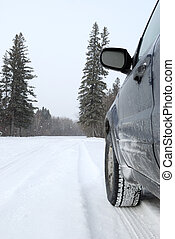 Winter Driving - A winter vehicle driving on snow covered...