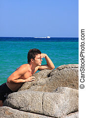 Young man relaxing by the sea in Greece