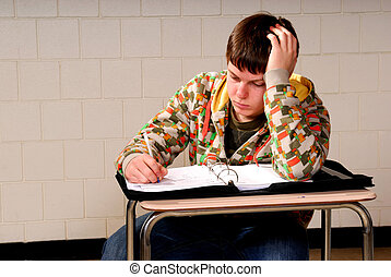 Teenager Taking Notes - A teenage boy writes in notebook...