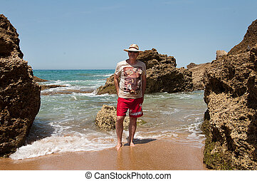 happy man with a straw hat in the ocean