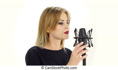 Young woman singing with studio microphone Isolated on white...